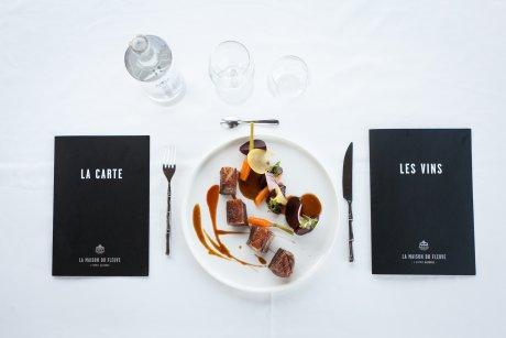 Une assiette, des verres et les carte de la Maison du Fleuve